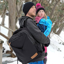 dad daughter at snow with nappy backpack