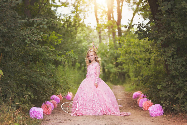 <alt>beautiful girl wearing a pink 3D flower lace dress posing in the woods with pretty paper pompoms</alt>