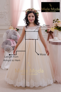 Flower girl wearing a cream lace dress and flower halo is standing in front of a window at miele moda boutique