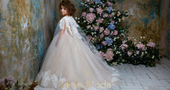 <alt>little girl wearing a pageant gown with cape and big bow handmade in Europe lace girl dress from miele moda boutique</alt>