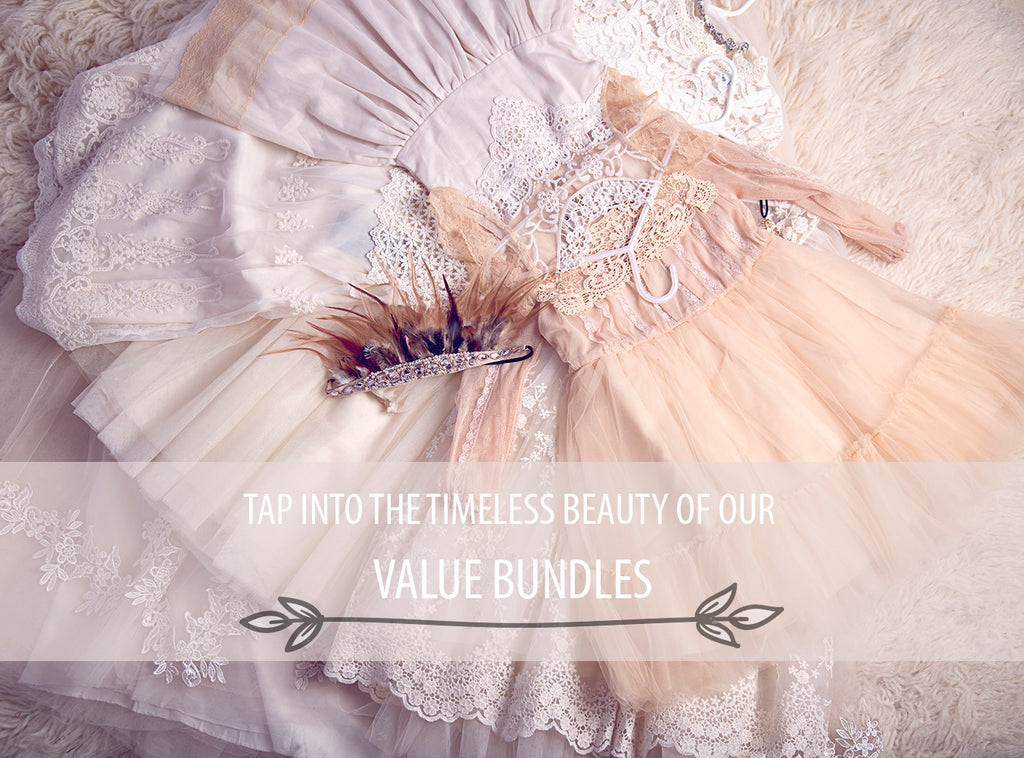 <alt>values bundles of beautiful lace dresses in neutral colors and a feathered headband laying on the floor</alt>