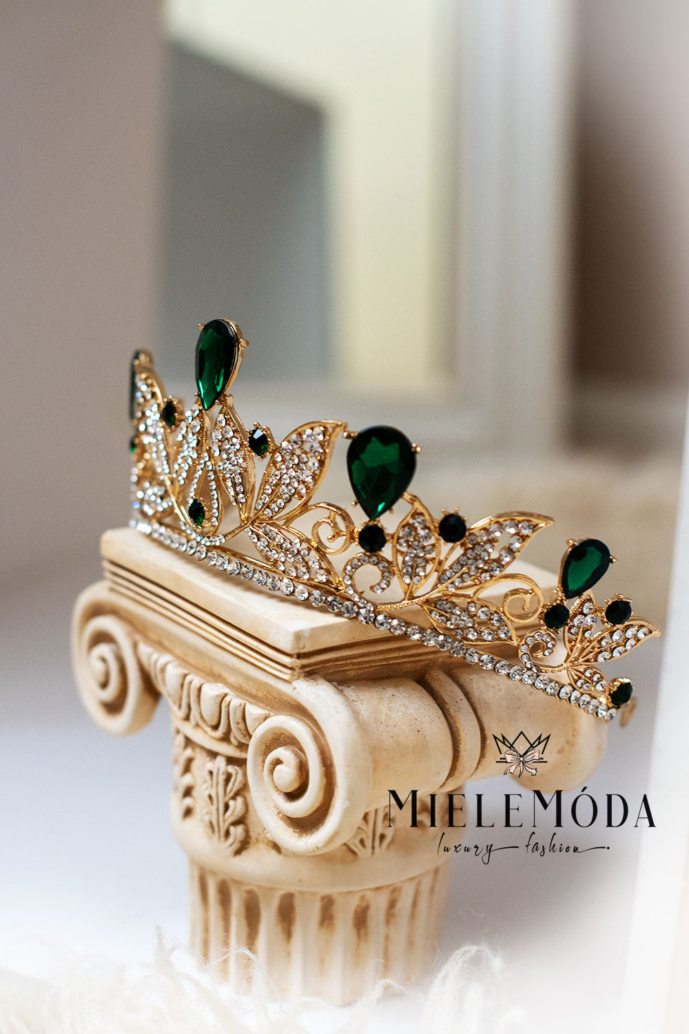 emerald and gold rhinestone crown princess tiara standing on a greek column