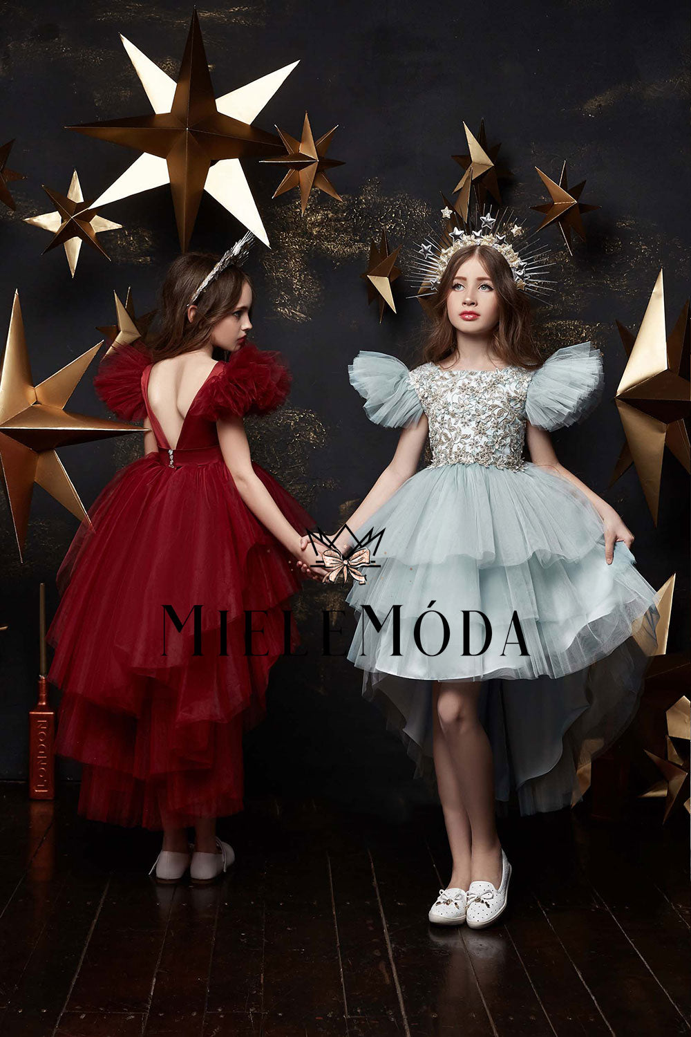 two girls are wearing pretty lace dresses in burgundy and gray and gold stars headpieces and posing in a photo studio