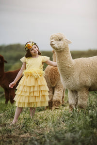 Pretty girl wearing Stellina Ruffle Tiered Flower Girl Dress-by Miele Moda Boutique
