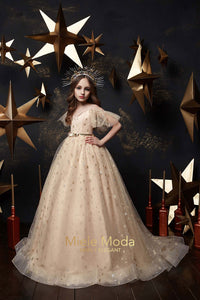 girl wearing beige special occasion dress with gold stars and beads and sparkling stars headpiece poses with her arms on her hips