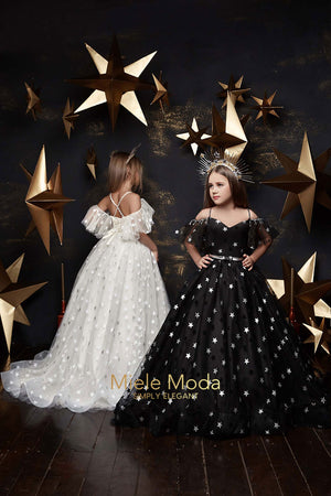 pretty girl models wearing star evening long dresses in ivory and black pose in front of a black and gold backdrop