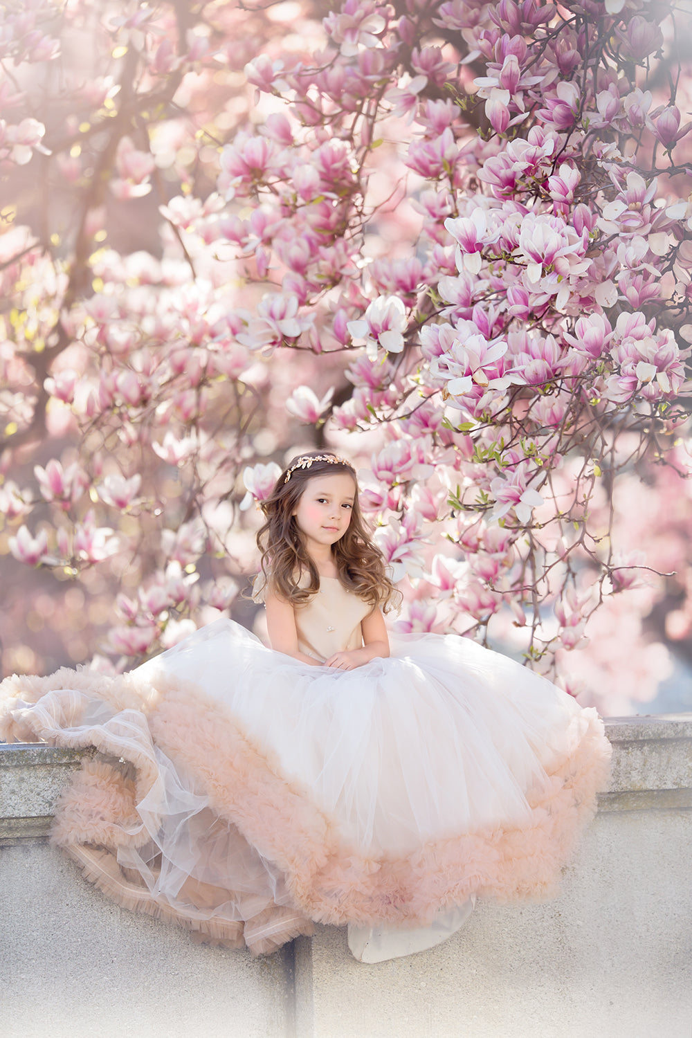 Pretty girl wearing special occasion ivory dress sitting in front of magnolia tree flowers Miele Moda Luxury Fashion
