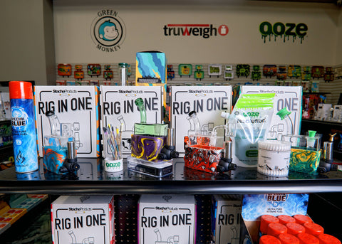 A close-up of a shelf in the Stache Rio merchandising display in the Cannatron wholesale showroom. Several Rios are out of the packaging, and one has a green Micro Rig inserted. A variety of different upselling accessories surround the rigs.