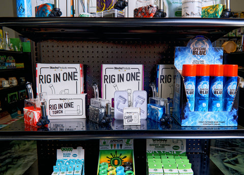 A close-up of a shelf of the Stache Rio merchandising display. There are 3 Rio dab rigs, two extra Stache bangers and a carb cap, and a display of Special Blue butane cans.