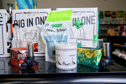 A close-up shot of the top shelf of the Stache Rio merchandising display. The green Rio has green Ooze Resolution res caps covering the openings, and is next to a pouch of Res Gel and box of cotton swabs.