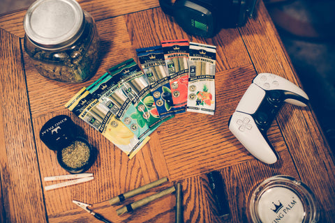 A variety of packs of different King Palm flavors are laid out in a fan shape on a wooden table. There is also a jar of weed, Xbox controller, and a few other accessories on the table.
