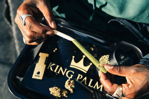 A black guy's hands are packing a King Palm cone using the included packing stick. He is doing this on a black rolling tray with a large gold King Palm logo with a matching grinder.