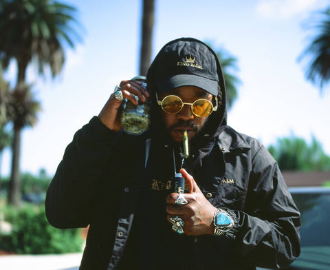 A young black guy wearing a King Palm hat and black jacket with the hood up is lighting a King Palm cone that is in his mouth. He is wearing glasses with yellow lenses, and it holding a jar of weed up to his ear like a phone.