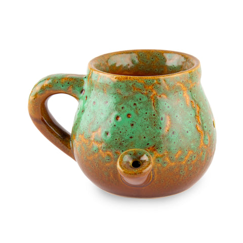 A round, short and squat green and gold ceramic glazed mug pipe sits against a white background.