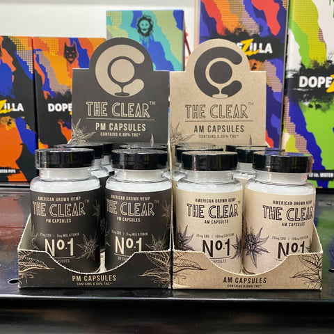 Two displays of The Clear CBD capsules sit together on a shelf in the Ooze Wholesale showroom. The left display is the PM capsules, with black branding and added melatonin, and on the right is the AM display with cream colored branding and added caffeine.