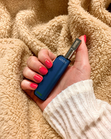 A white female hand with pink nail polish holds a blue Ooze Novex battery with a chrome Ooze atomizer. She wears a white ribbed sweater and her arm is laying on a fuzzy tan blanket