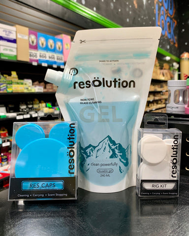 Resolution Colorado cleaning solution in a large pouch with a dispensing spout, and two packs of Resolution silicone cleaning caps sit on a shelf in the Ooze Wholesale showroom.