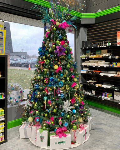 The festive Christmas tree set up in the Ooze Wholesale showroom. It has pink, purple, turquoise and green ornaments, a big fancy tree topper, and is surrounded by Ooze boxes wrapped with ribbons.