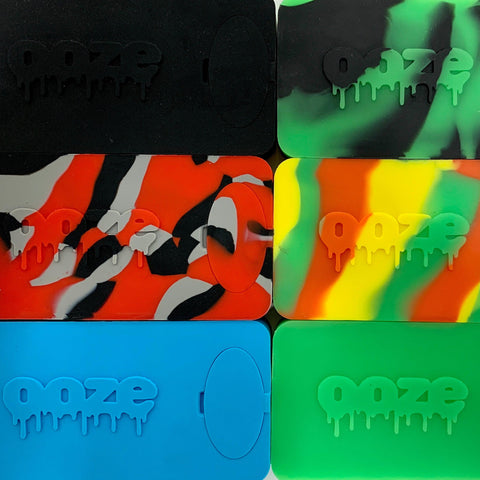 An up-close, flat lay shot of all 6 colors of the Ooze Slugger Dabbin Dugout. 2 columns of 3 Sluggers each: black, green-black mix, red-black-gray tie dye, Rasta tie dye, teal, and green.