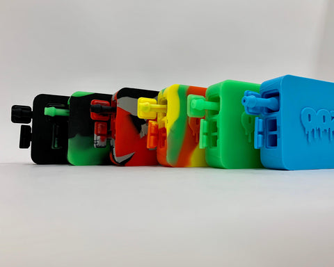 All 6 Ooze Slugger Dabbin Dugout colors are lined up against a white background. They stand on their side with the bottom flaps open, exposing the nectar collector straw. The colors from left to right are black, green-black mix, red-black-gray tie dye, Rasta tie dye, green, and teal.