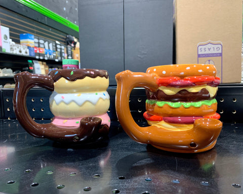Two food mug pipes sit next to each other on a black tabletop. The donut mug is on the left and the cheeseburger mug is on the right, both have the bowl showing.