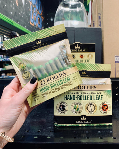 A female hand holds the 25 pack of King Palm Rollies pre-rolled wraps in front of the counter display.