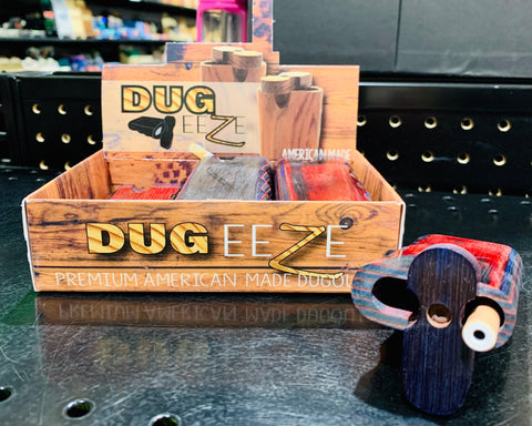 A display of the Dug-Eeze dugouts on a black table top with one dugout outside of the display box with the top open exposing the one hitter and opening.