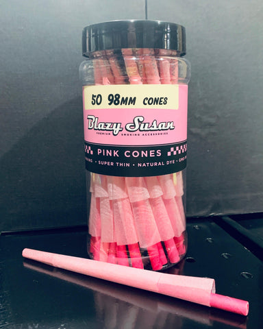 A 50ct pack of Blazy Susan pink pre-rolled cones sits on a black shelf. A single pink cone with a packing stick lays on the shelf in front of the package.