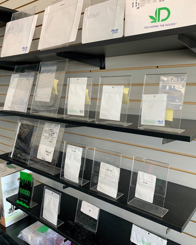 A full wall of different sizes of Mylar and Exit bags for dispensaries. Each is shown in a clear plastic stand, and they are arranged in a row on a full wall of shelves.