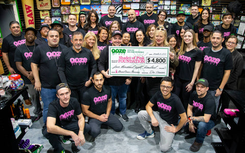 The entire Ooze Wholesale team is gathered in the old showroom and are wearing matching black shirts with pink Ooze logos. In the center is the director from the Shades of Pink Foundation holding a large check for $4,800 which was the Ooze donation.