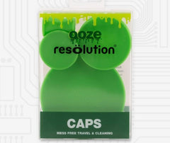 A 4-pack of green Ooze Resolution silicone cleaning caps in the original packaging are shown against a light background with a faint pattern that resembles a control panel.