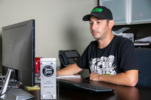 Ooze Wholesale CFO Vince Ayar sits at his desk working on the computer. He wears an Ooze baseball hat, Monsterous shirt, and has the 2019 Inc. 500 plaque just out of focus in the front of the shot.