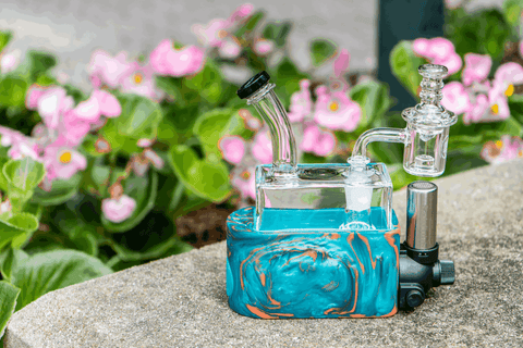 Blue Stache RiO Rig In One in front of pink flowers