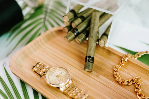 A clear plastic box full of King Palm cones is laying on its side with one cone pulled out onto the light wash wooden rolling tray. There is a gold watch and gold chain also on the tray, and fern leaves on the table underneath.