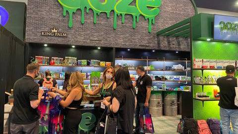 The Ooze tradeshow booth is set up and being visited live at a show. There is a group of people gathered around the front table, and a few people browsing the shelves behind them and to the right.
