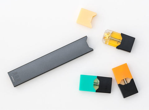 A Juul e-cigarette is laying on a white background with three unused pods laying to the right. There is a pod with a mint cap, an orange cap, and a pod with the yellowish cap removed.