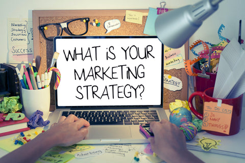 What is your marketing strategy? On Laptop Screen with corkboard behind at messy desk