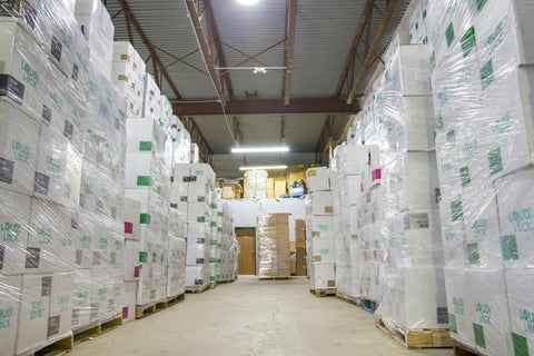 A wide shot of an aisle in the Ooze Wholesale warehouse. You can see both sides are stacked to the ceilings with white Loud Lock boxes on pallets and wrapped.