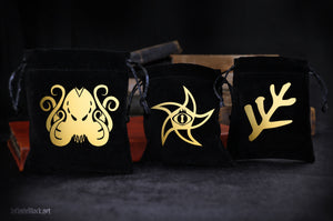 The collection of black velvet dice bags featuring symbols of the Cthulhu Mythos