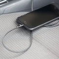 An iPhone charging cable charging an iPhone in a car