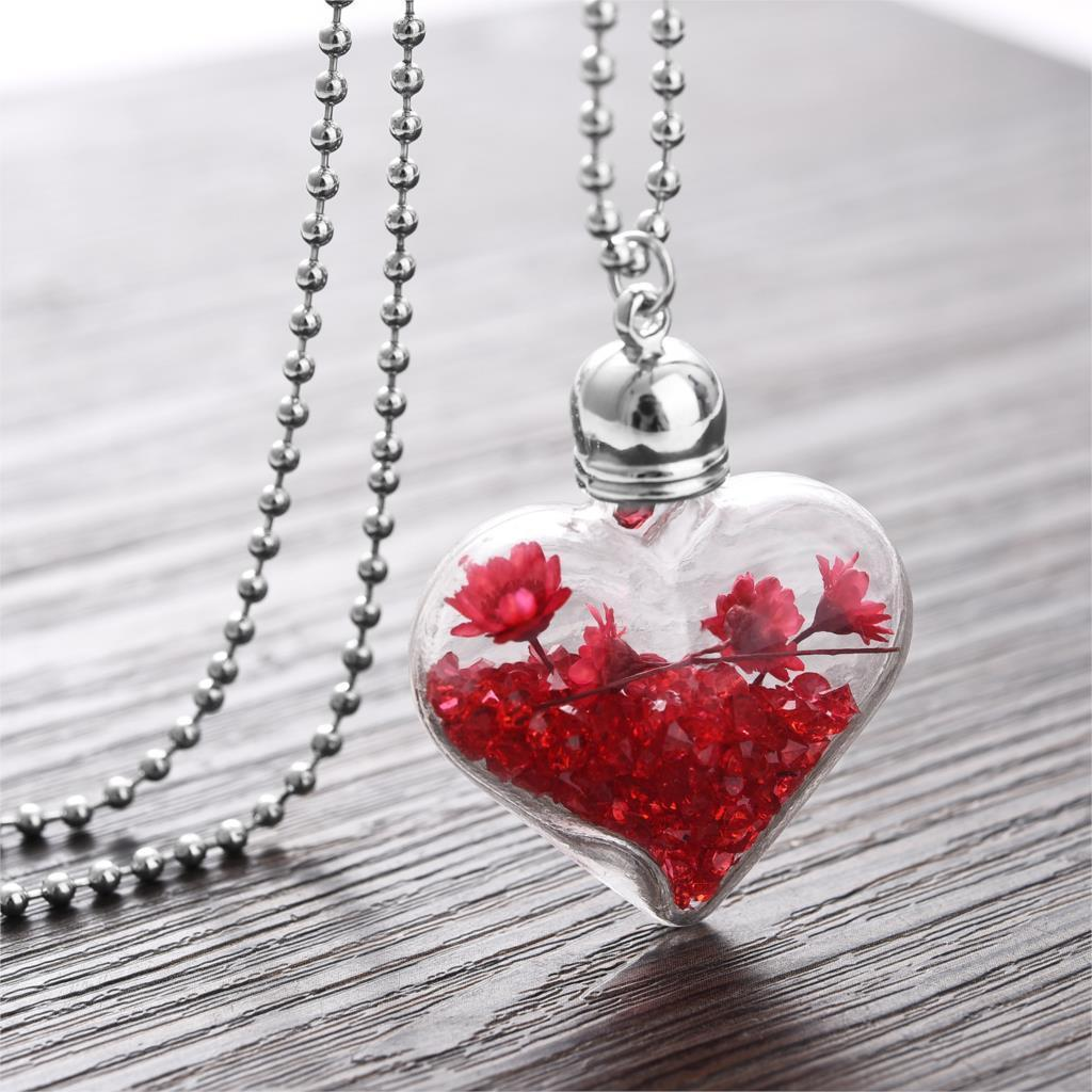 Necklace and heart shaped glass vial with dried flowers and crystals
