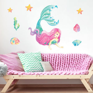 Mermaid wall stickers stuck onto a cream bedroom wall above a pink wooden sofa.