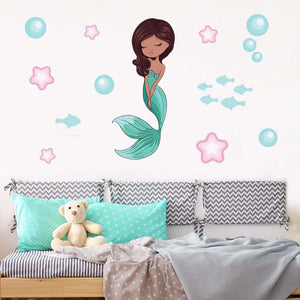 Mermaid wall stickers stuck on a cream wall above a white wooden sofa. Sofa has cushions an teddy on it.