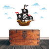 Cartoon pirate ship wall sticker stuck on white wall above a wooden looking treasure chest furniture.