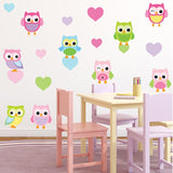 Cheeky baby owls wall stickers stuck on childs wall. Wall is pink, kids chair is pink purple colour.