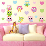 Cheeky baby owls wall stickers stuck on living room wall, above sofa. Wall is cream sofa is purple pink pillows.
