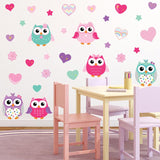Colorful owls wall stickers stuck on playroom wall above children desks.