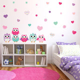 Colorful owls wall stickers stuck on girls bedroom wall. Pink an purple theme bedroom.