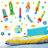 colourful rocket wall stickers set displayed above colourful bed on bedroom wall.