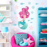 Mermaid wall stickers stuck on a girls white bedroom wall above a pink sofa.